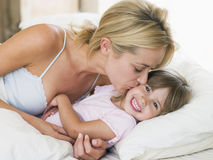 Woman kissing young girl in bed smiling Stock Image