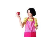 Woman in kitchen apron holding apples Royalty Free Stock Images