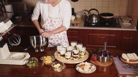 A woman in a kitchen apron lays a sweet cream in glasses with fruit and berries. A woman in a kitchen apron who looks like a cook, puts sweet vanilla cream in stock footage