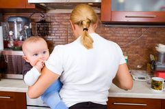 Woman in kitchen with a baby Stock Image