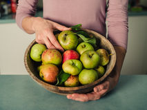 Woman in kitchen with bowl of apples Royalty Free Stock Photo