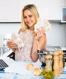Woman in kitchen with cash Stock Photos