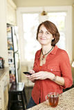 Woman in kitchen with cell phone Stock Photos