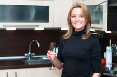 Woman in kitchen with champagne Stock Photo