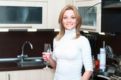 Woman in kitchen with champagne Royalty Free Stock Photo