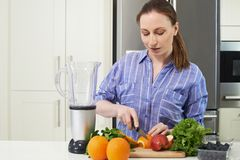 Woman In Kitchen Chopping Fruit To Put Into Juicer. Woman In Kitchen Chops Fruit To Put Into Juicer Stock Photography