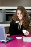 Woman in kitchen with coffee looking at laptop Royalty Free Stock Images