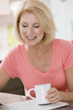 Woman in kitchen with coffee and newspaper smiling Stock Image