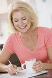 Woman in kitchen with coffee and newspaper smiling Royalty Free Stock Photography