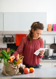 Woman in kitchen comparing shopping list to items in bag Royalty Free Stock Image