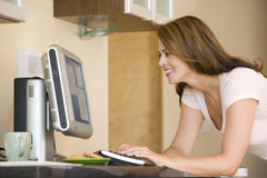 Woman in kitchen with computer Stock Images