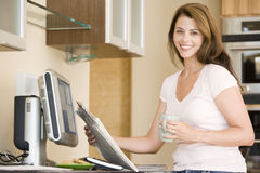 Woman in kitchen at computer with coffee Royalty Free Stock Photography