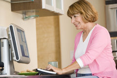 Woman in kitchen with computer and coffee smiling Royalty Free Stock Photo
