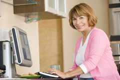 Woman in kitchen with computer and coffee smiling Stock Photo
