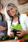 Woman in kitchen cooking with help of husband Royalty Free Stock Image