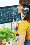 Woman in kitchen cooking with listening music Stock Images