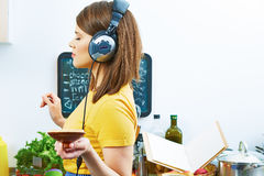 Woman in kitchen cooking with listening music