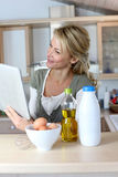 Woman in kitchen cooking and searching for recipe Royalty Free Stock Images