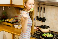 Woman cooking stir fry frozen vegetable on pan. Woman in kitchen cooking stir fry frozen vegetables on pan and tasting. Girl frying making delicious dinner food stock images