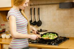 Woman cooking stir fry frozen vegetable on pan. Woman in kitchen cooking stir fry frozen vegetables on pan and tasting. Girl frying making delicious dinner food stock photos