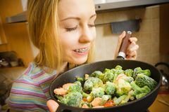 Woman cooking stir fry frozen vegetable on pan. Woman in kitchen cooking stir fry frozen vegetables on pan and tasting. Girl frying making delicious dinner food stock image