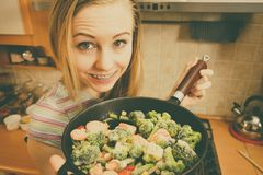 Woman cooking stir fry frozen vegetable on pan. Woman in kitchen cooking stir fry frozen vegetables on pan and tasting. Girl frying making delicious dinner food royalty free stock photos