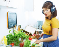 Woman in kitchen cooking vegetable.