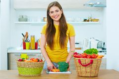 Woman in kitchen cooking vegetables. Young woman with long hair casual clothes wearing Royalty Free Stock Images