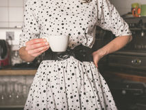 Woman in kitchen with cup of coffee Stock Photography