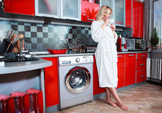 Woman in the kitchen with cup tea Royalty Free Stock Images