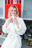 Woman in the kitchen with cup tea Stock Image