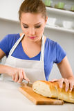 Woman in kitchen cutting bread Royalty Free Stock Photography