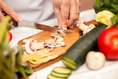 Woman in the kitchen cutting champignons Royalty Free Stock Photography