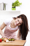 Woman in kitchen cutting paprika Royalty Free Stock Image