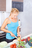 Woman in kitchen cutting vegetables. Young woman in kitchen cutting vegetables royalty free stock photography