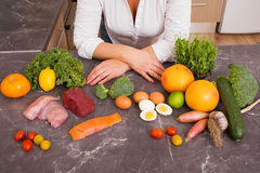 Woman in kitchen with different raw foods Royalty Free Stock Photos