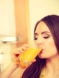 Woman in kitchen drinking fresh orange juice Royalty Free Stock Image