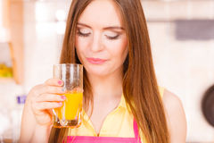 Woman in kitchen drinking fresh orange juice Stock Photography