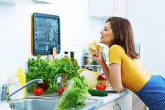 Woman in kitchen eating banana. Stock Photography