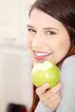 Woman in kitchen eating green apple stock photography