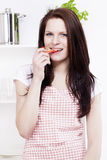 Woman in a kitchen eating paprika Stock Images