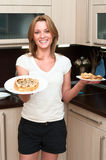Woman in kitchen with flapjacks on plates Royalty Free Stock Image