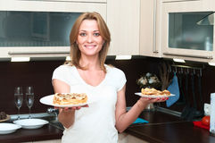 Woman in kitchen with flapjacks on plates Royalty Free Stock Photography