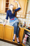 Woman on kitchen furniture eat long noodle Stock Photo