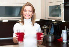 Woman in kitchen with glasses of juice Stock Photography