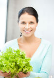 Woman in the kitchen with green salad leaves Royalty Free Stock Photography