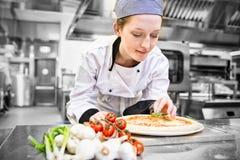 Woman kitchen help preparing pizza Stock Photography