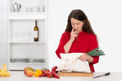 Woman in the kitchen with her food shopping Stock Images