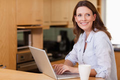 Woman in the kitchen with her notebook Royalty Free Stock Image