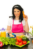 Woman in kitchen holding carrot Royalty Free Stock Image